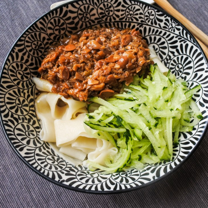 a bowl of Chinese noodles with grated cucumber and soy bean sauce