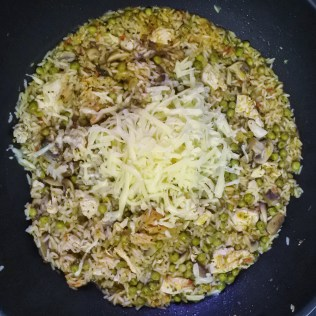 cooked rice mixture with grated cheese on top