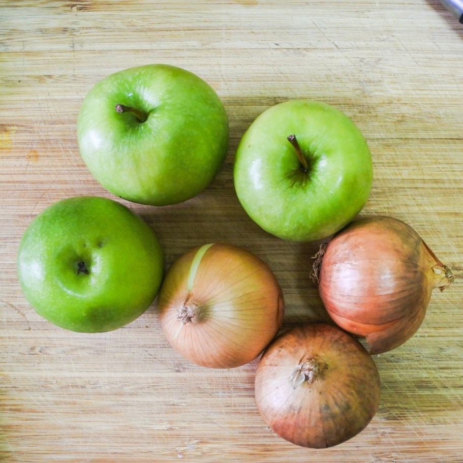 green apples and onions on a cutting board