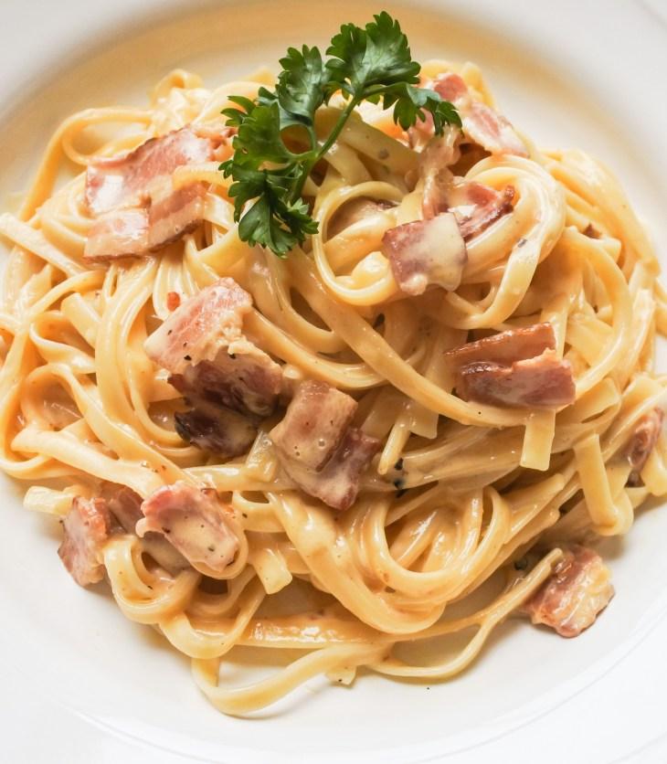 Creamy carbonara pasta garnished with a sprig of parsley