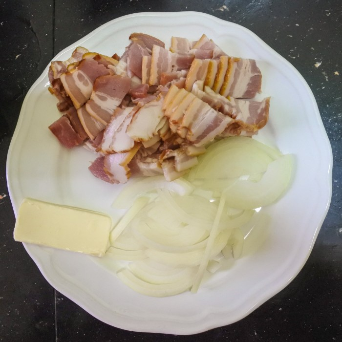 Sliced onions, bacon and a pat of butter on a plate