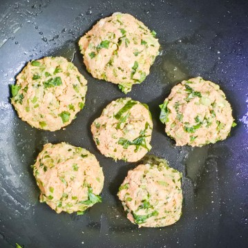 salmon cakes frying in a pan