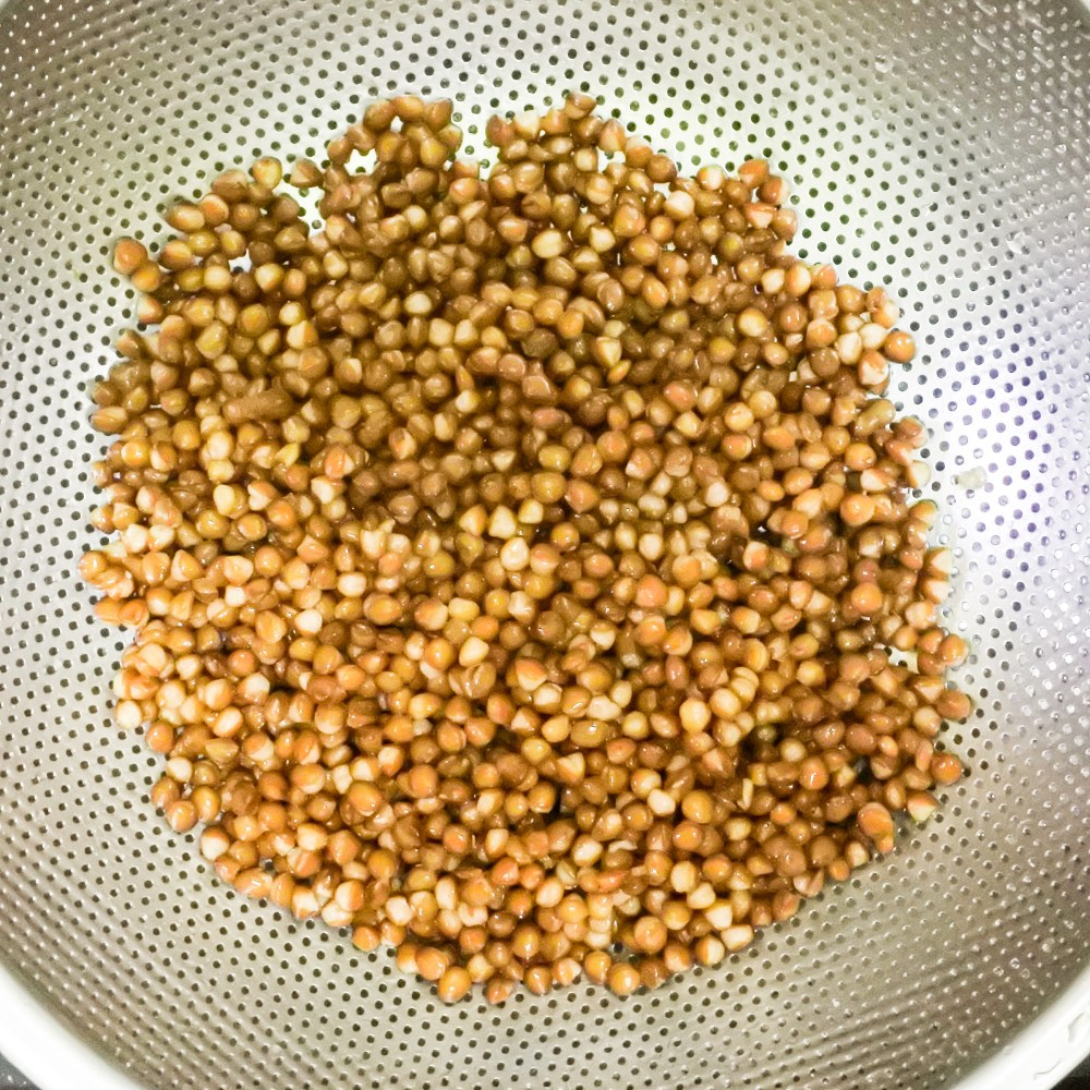 Drained lentils in a metal colander