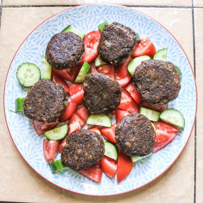 Vegetarian lentil burgers over a tomato and cucumber salad