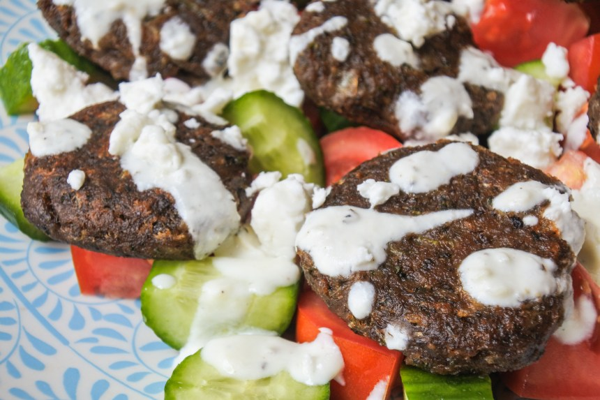 Lentil cakes over a salad of cucumber and tomato salad topped with a yogurt dressing and feta cheese