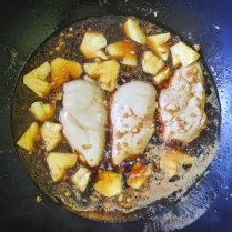 Chicken breasts and pineapple cooking in soy mixture