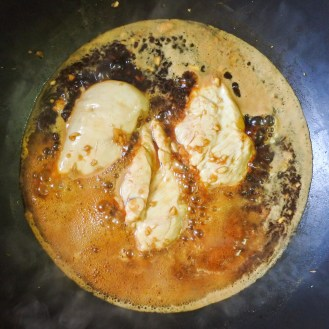 chicken breasts cooking in soy mixture