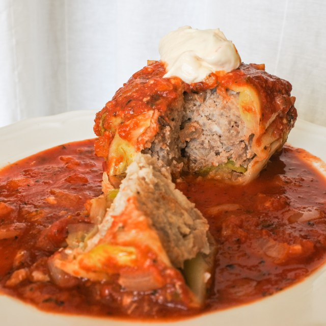 stuffed cabbage covered in tomato sauce and topped with sour cream