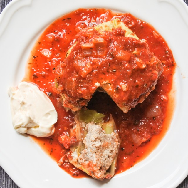 stuffed cabbage covered in tomato sauce with a side of sour cream
