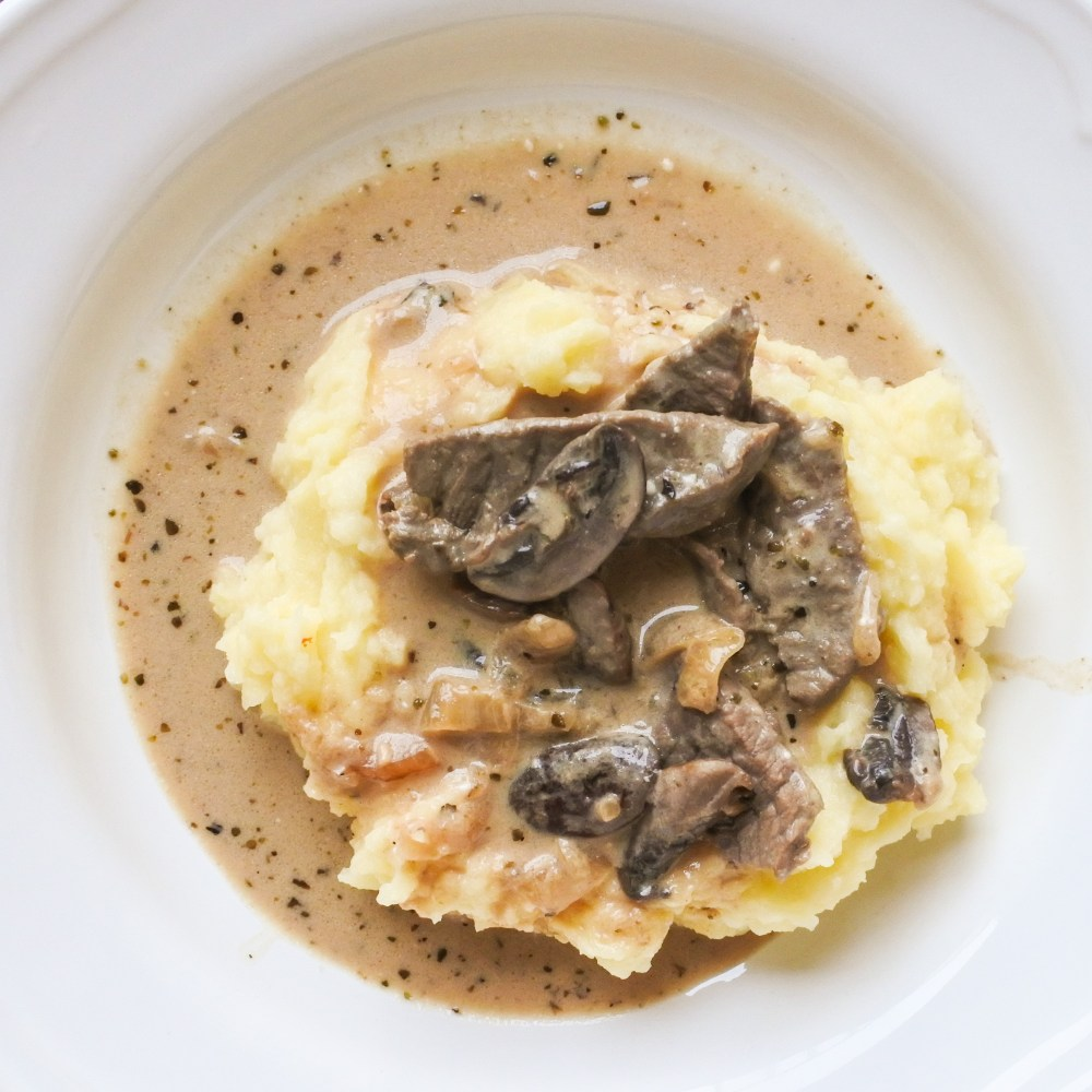 Beef and mushroom Stoganoff served atop a pile of mashed potatoes