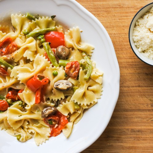 Farfalle pasta tossed with roasted vegetables and cream served alongside grated Parmesan cheese