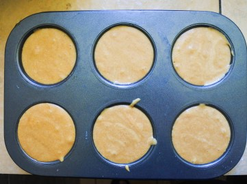 Grease muffin tin or a medium sized cake pan with butter. If you are using cupcake wrappers, don't grease. Pour mixture into muffin tins or pan and place in oven.