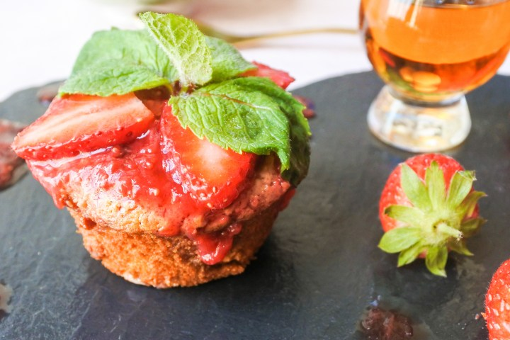 Dulce de leche cupcake topped with strawberry sauce, sliced strawberries and a sprig of mint with a glass of whisky and strawberries