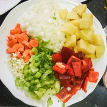 Dice the onions and mince the garlic. Chop the carrot, celery, red bell pepper and potato into bite sized pieces about 1 inch/ 2 cm big.