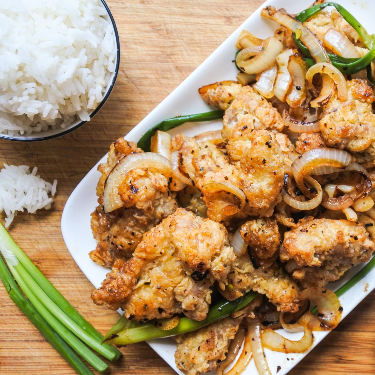 Salted fried chicken with scallions and onions served with a bowl of rice