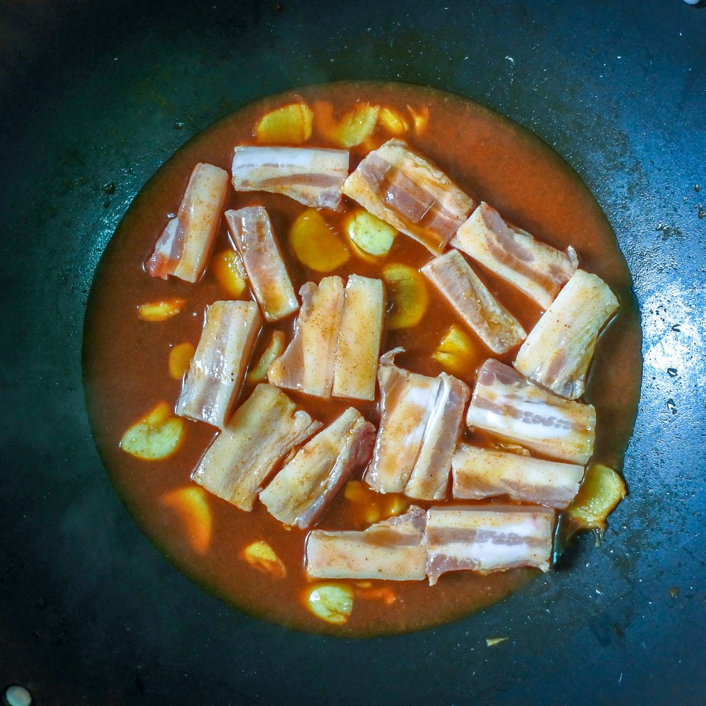 Pork belly pieces sauteing in Thai chile broth