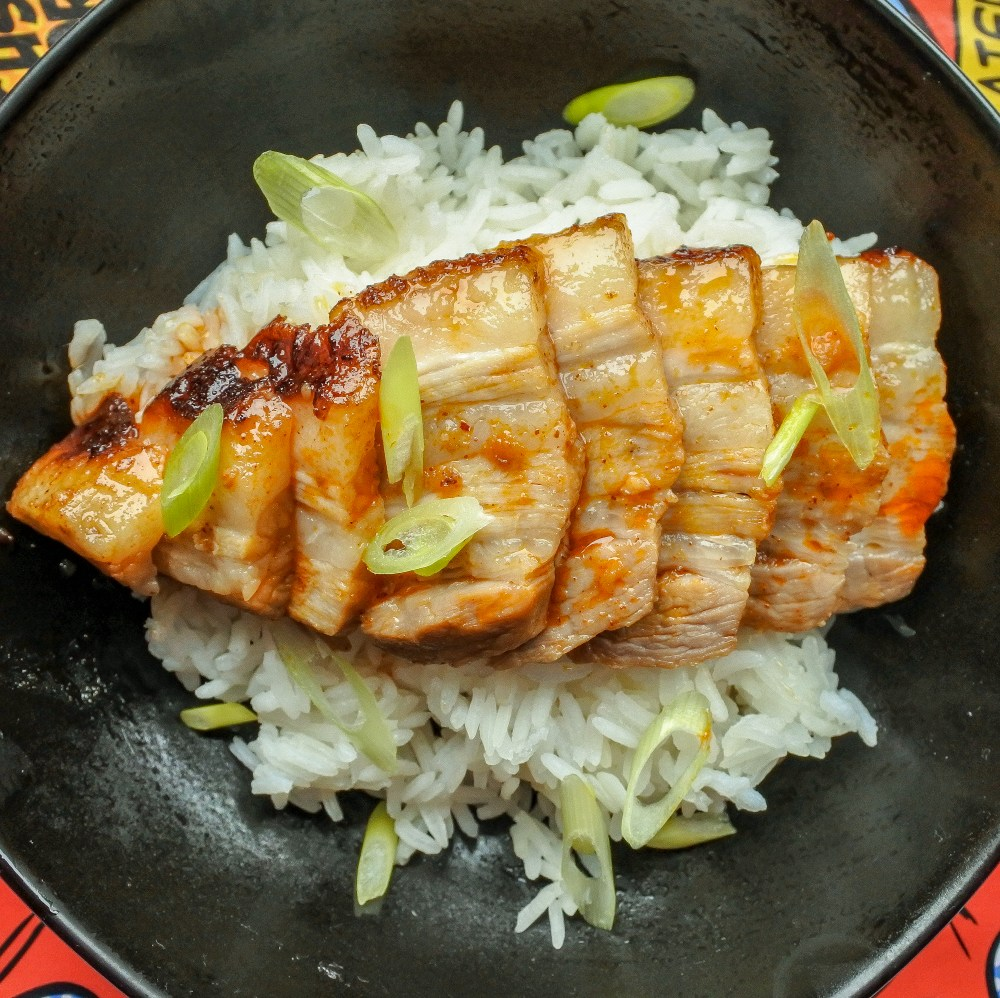 sliced pork belly over jasmine rice garnished with chopped scallions in a black bowl