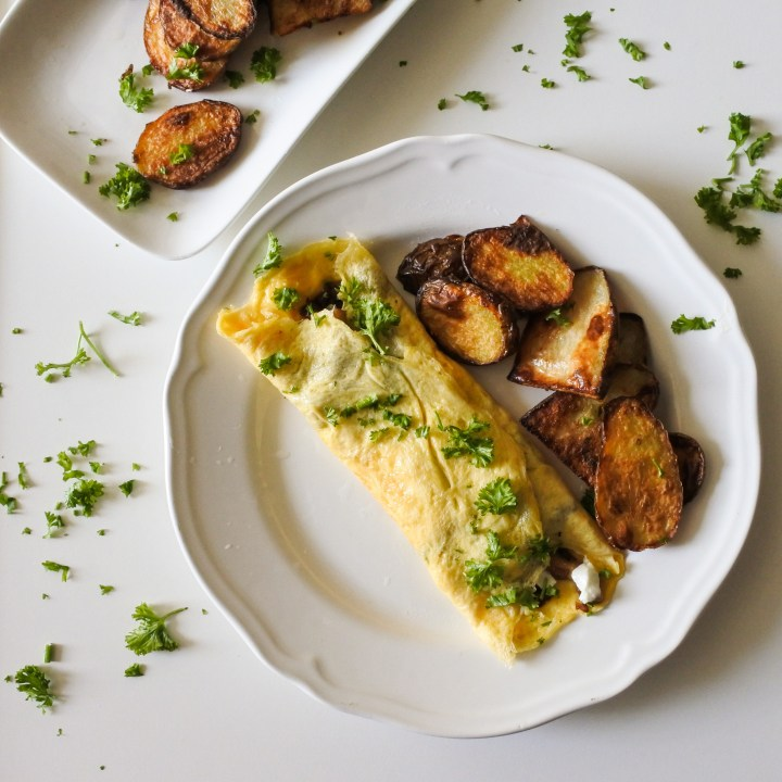 A French omelette garnished with chopped parsley served alongside roast potatoes