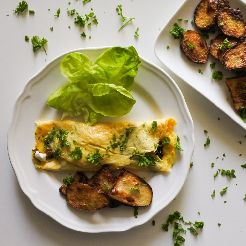 A French omelette garnished with chopped parsley served alongside roast potatoes and lettuce leaves