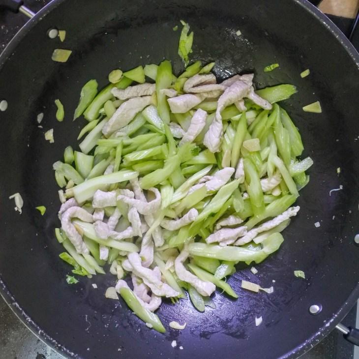 pork and celery frying in wok
