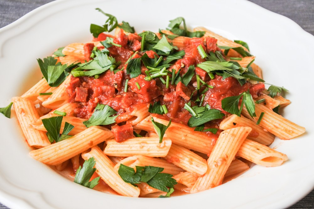 Penne pasta covered in a tomato and chorizo sauce garnished with Italian parsley