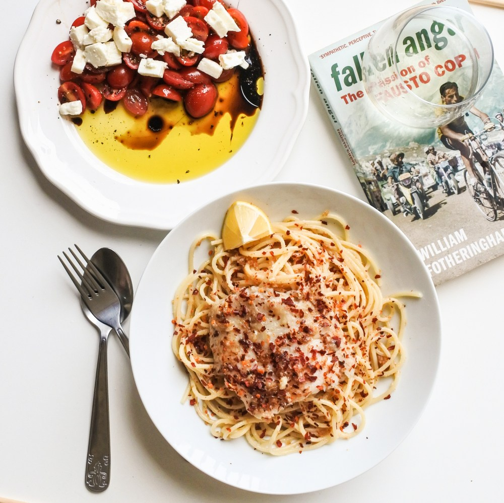 A bowl of spaghetti topped with white fish and red pepper flakes served alongside a tomato feta salad, glass of white wine and cycling book