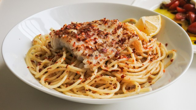 A bowl of spaghetti topped with white fish, a lemon wedge and red pepper flakes served alongside a tomato feta salad
