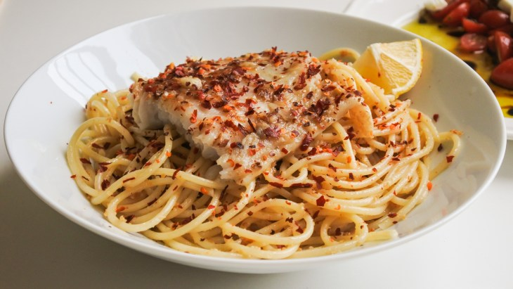 Anchovy pasta topped with white fish, a lemon wedge and red pepper flakes served alongside a tomato feta salad