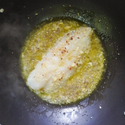 White fish being added to a simmering white wine and anchovy sauce