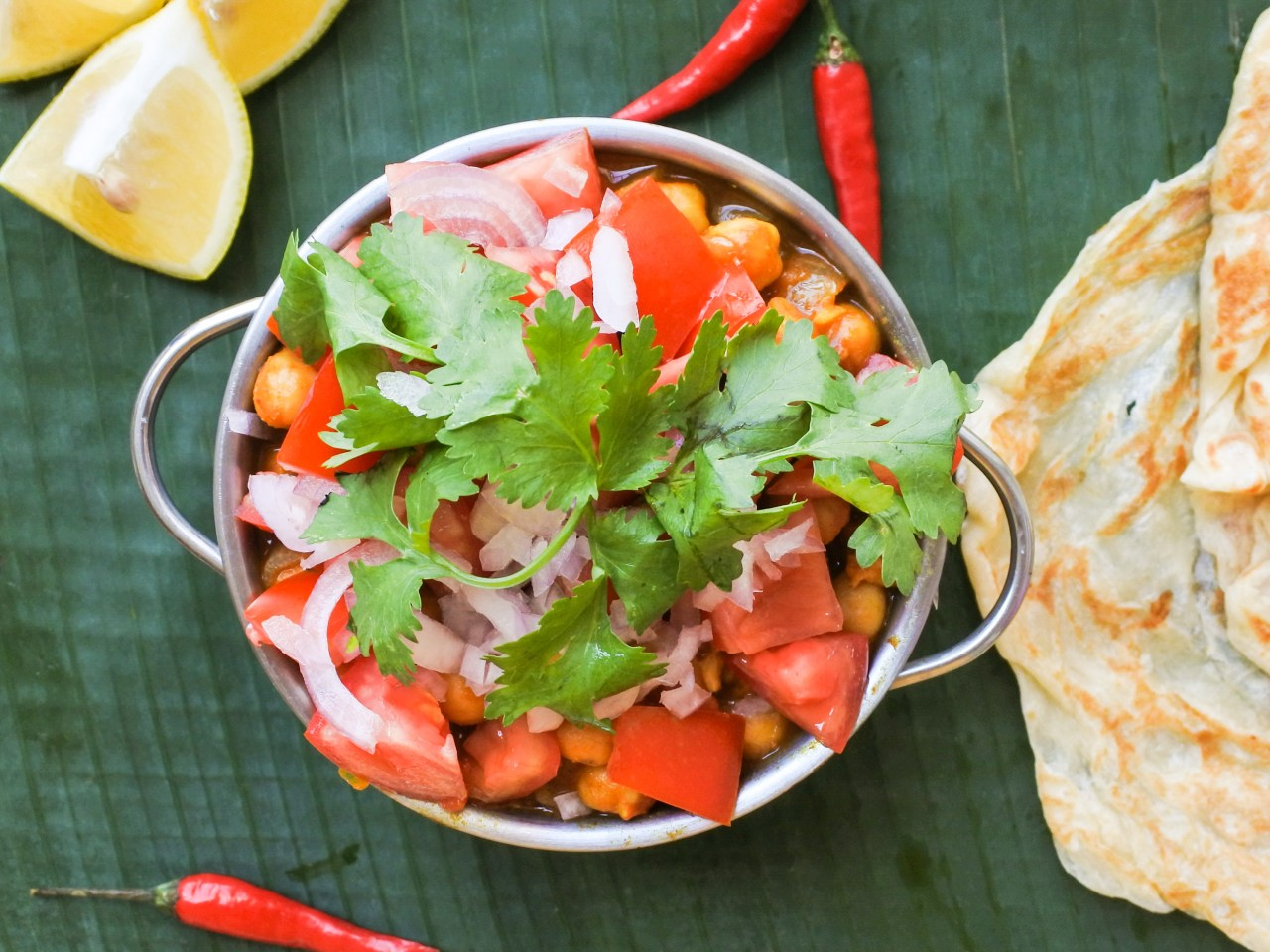 A bowl of curried chickpeas garnished with chopped tomatoes, red onions and cilantro served alongside lemon wedges, red chiles and roti