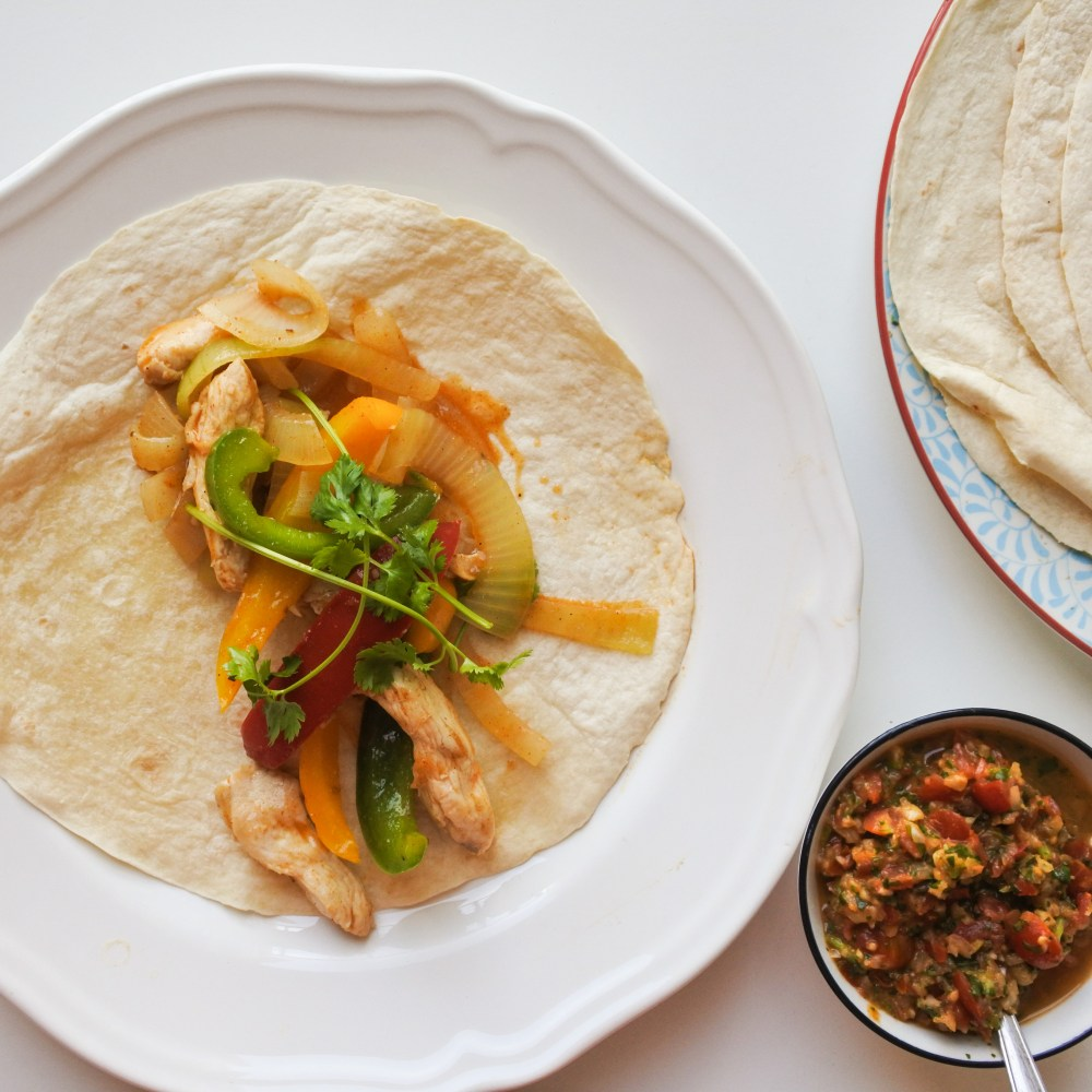 Chicken fajitas in the center of a flour tortilla served alongside fresh salsa