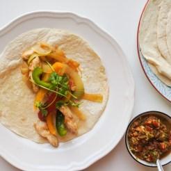 Chicken fajitas in the center of a flour tortilla served alongside fresh salsa
