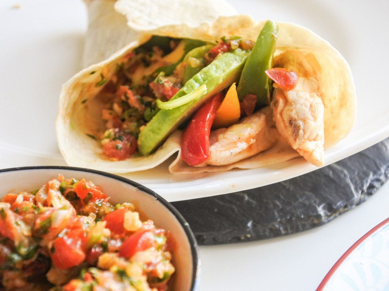 Chicken fajitas, salsa and avocado wrapped around a folded tortilla served alongside a small bowl of salsa