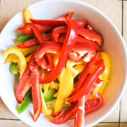 Chopped strips of bell peppers in a large bowl