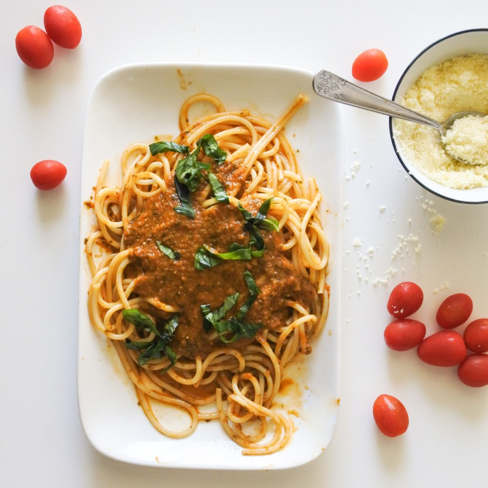 A plate of spaghetti covered in red sauce and garnished with chopped Basil served alongside cherry tomatoes and grated Parmesan cheese