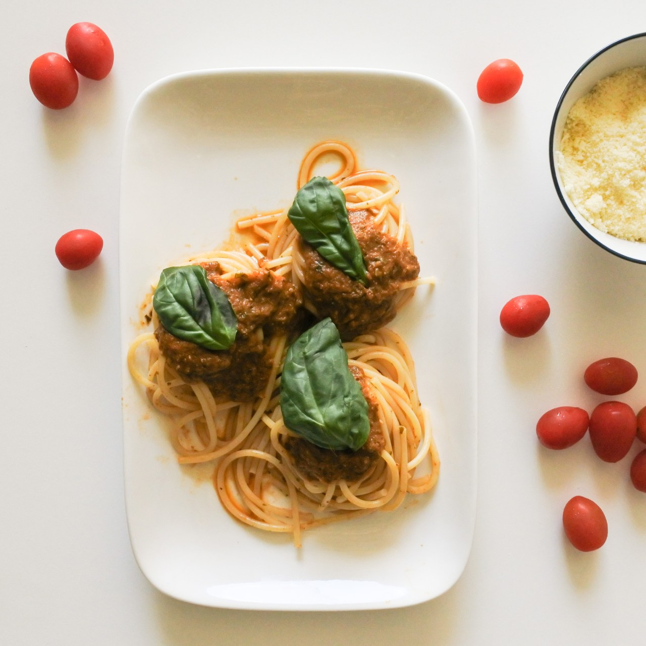 A plate of spaghetti covered in red sauce and garnished with Basil served alongside cherry tomatoes and grated Parmesan cheese