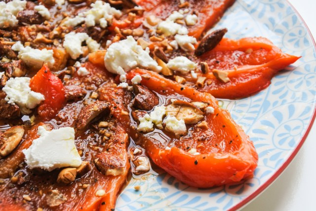 A flower of roasted red peppers topped with white goat cheese and roasted almonds