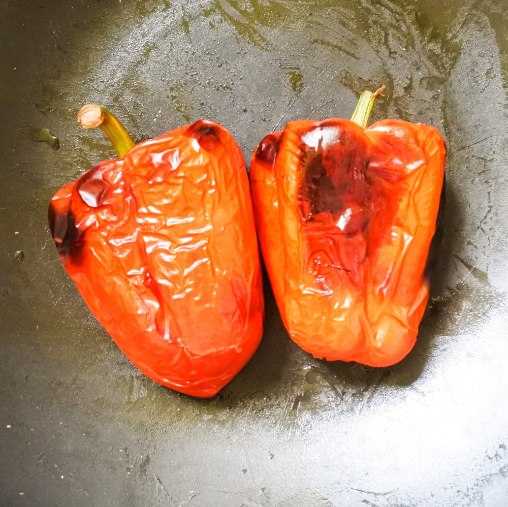 Blistered capsicums put into a large pot to steam