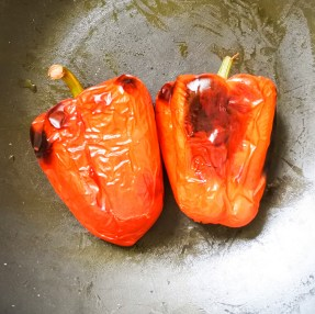 Roasted red peppers put into a large pot to steam