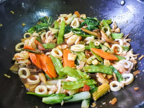 Vegetables and seafood cooking in a red Thai Chile sauce in a large wok