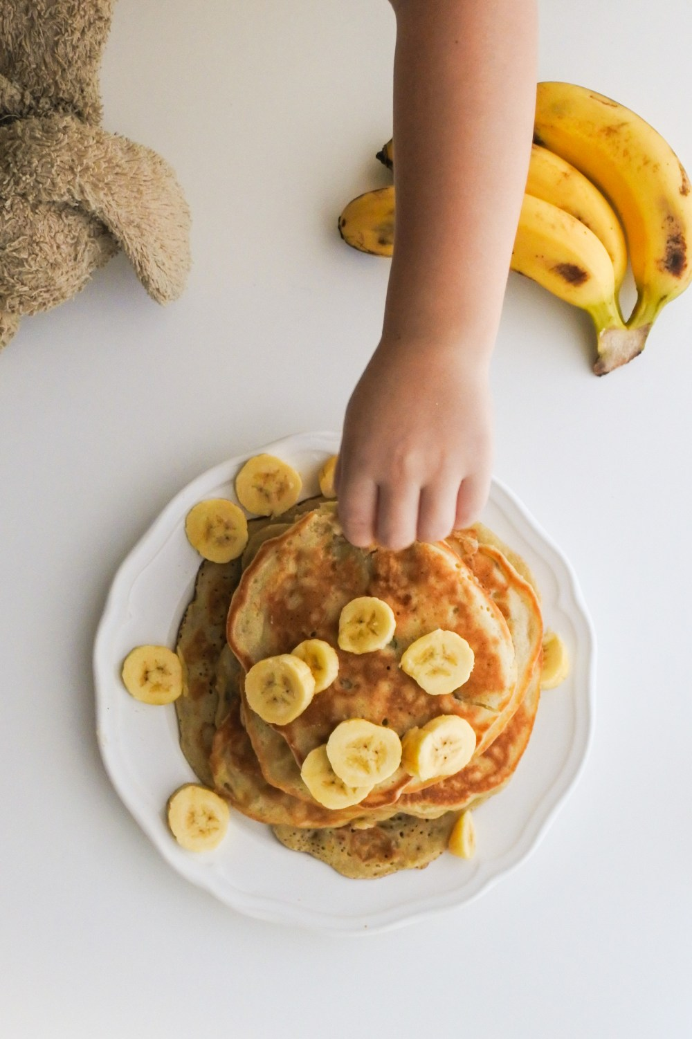 A little hand grabbing a banana slice on top of a stack of pancakes alongside a child's stuffed animal and small bunch of bananas