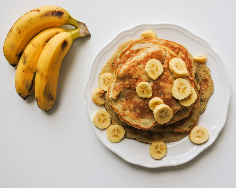 A stack of pancakes topped with sliced bananas and served alongside a small bunch of bananas