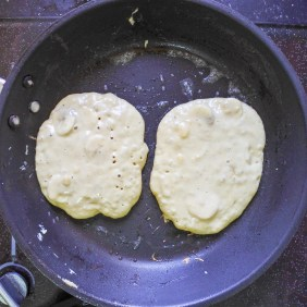 Two pancakes with a bubbled surface cooking in a pan