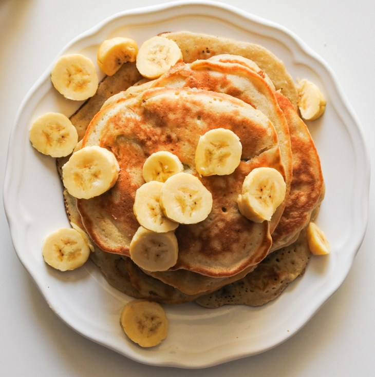 A stack of pancakes topped with sliced bananas on a white plate