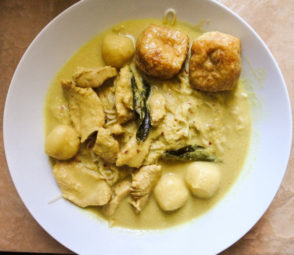 Curry laksa served over noodles with chicken, fish balls, tofu puffs and curry leaves