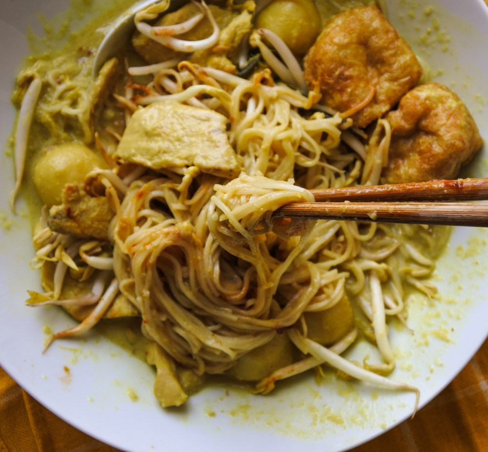 Noodles tossed in a yellow curry laksa broth with chicken, tofu puffs, bean sprouts and fish balls