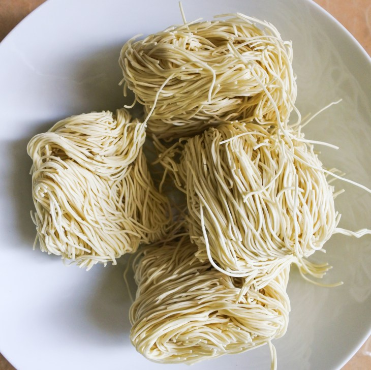 Bundles of uncooked white Chinese alkaline noodles in a white bowl