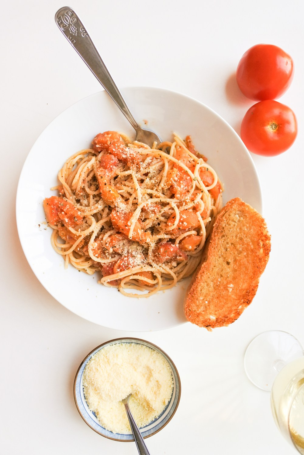 A plate of spaghetti tossed with roasted tomatoes and dusted with Parmesan cheese served with garlic bread