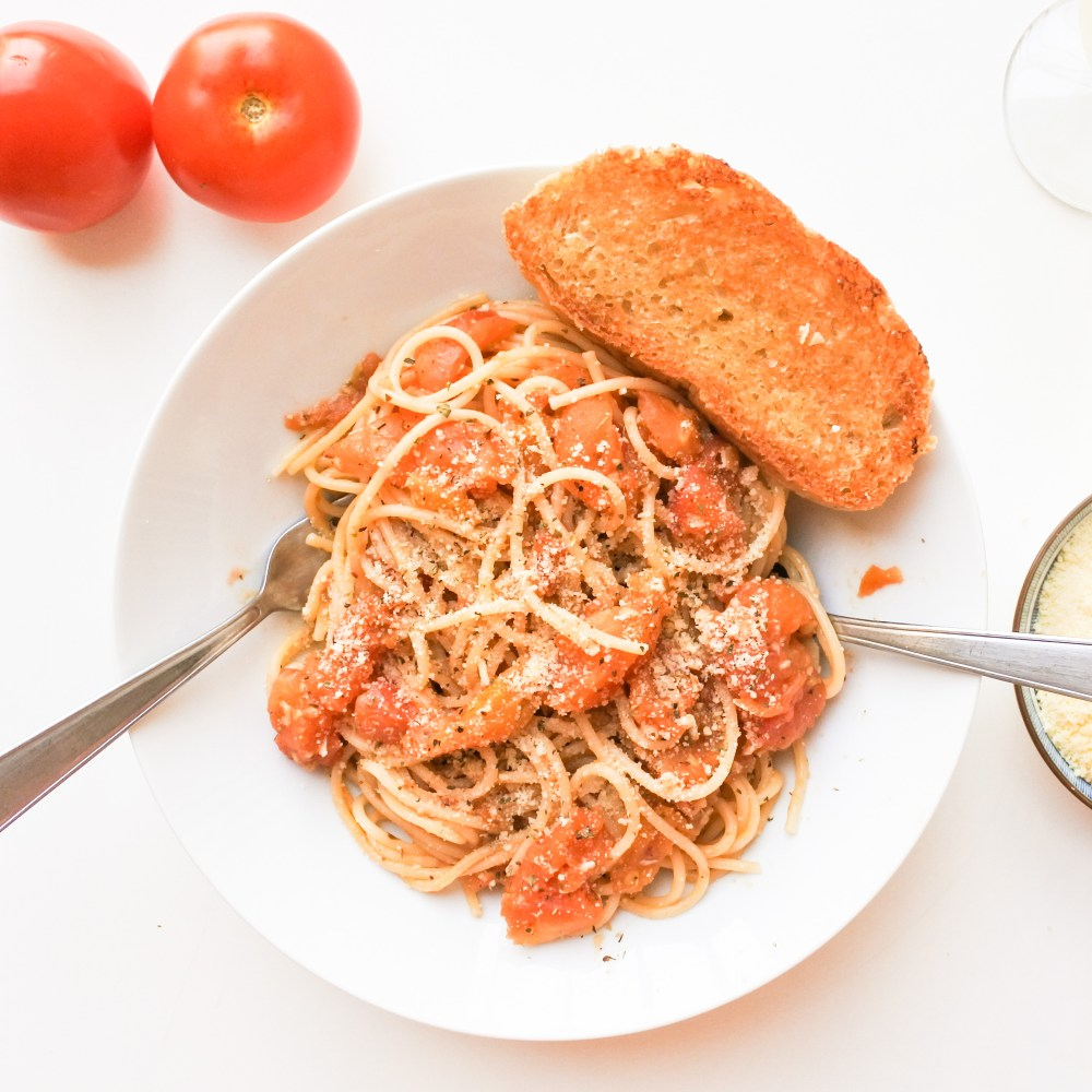 A fork and spoon dug deep into a plate of spaghetti with garlic bread