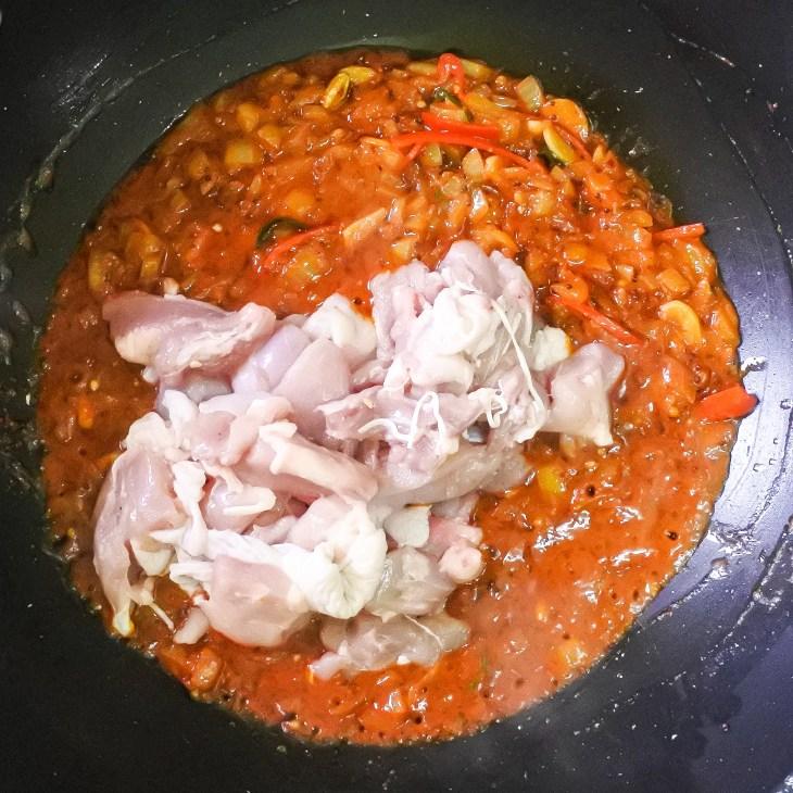 raw chicken added to balti curry gravy in wok
